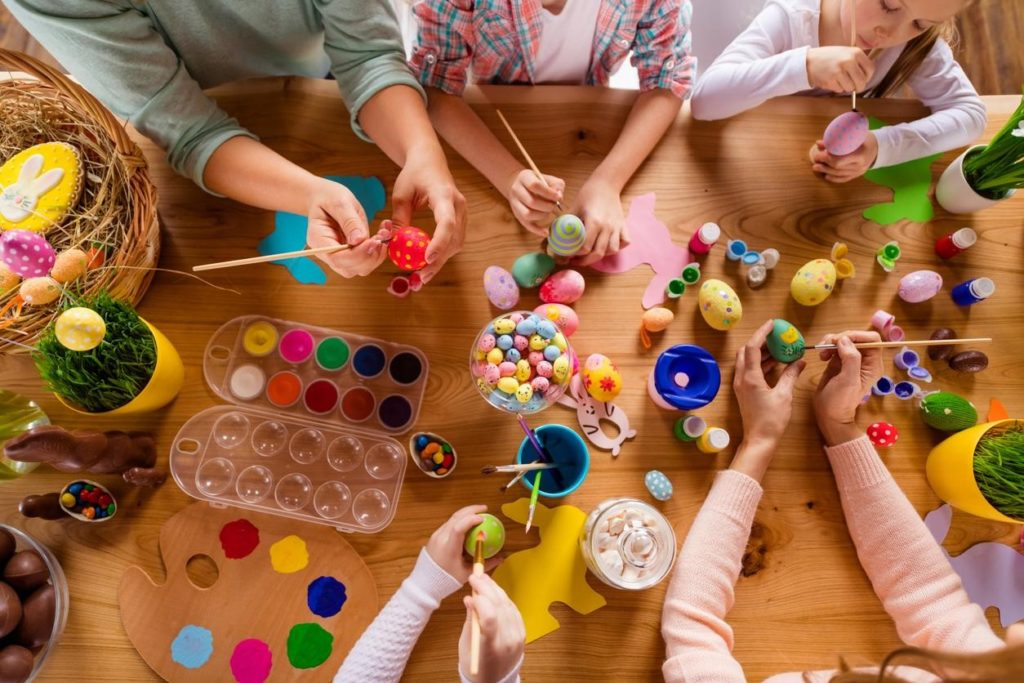 Family decorating easter eggs at the kitchen table, at-home Easter activities concept